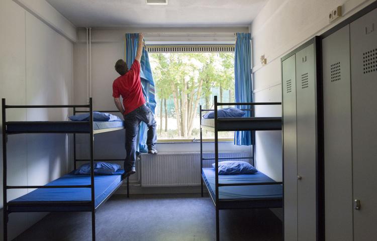 COA-medewerker hangt gordijnen op in kamer van azc