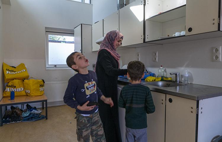 Vrouw met twee kinderen in hun kamer in het azc