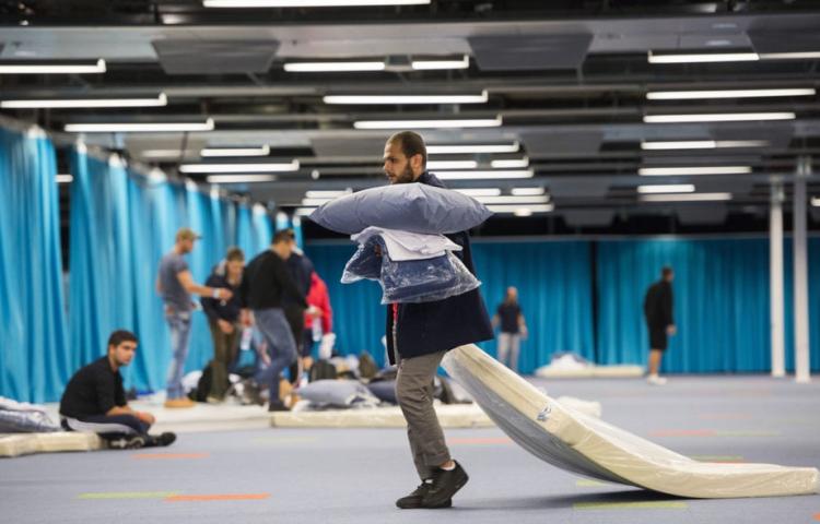 Vluchteling sleept met een matras in Jaarbeurs Utrecht