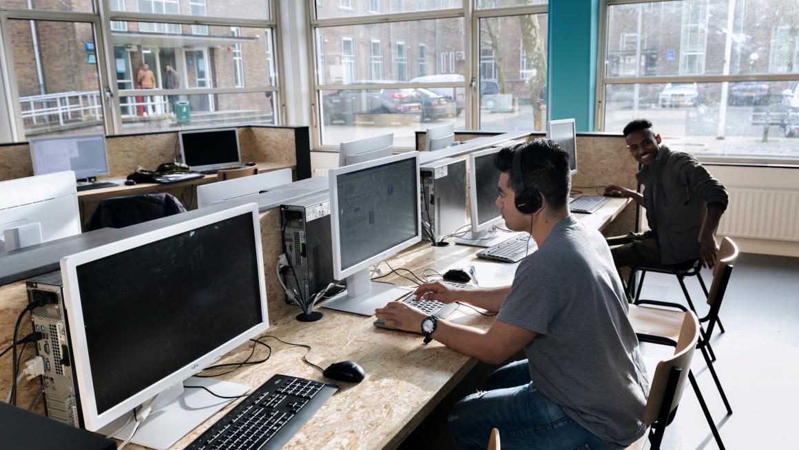 Asielzoekers werken achter computer in open leercentrum van azc