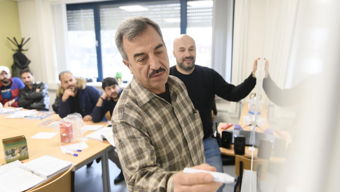Statushouder schrijft op whiteboard tijdens les Kennis van de Nederlandse Maatschappij