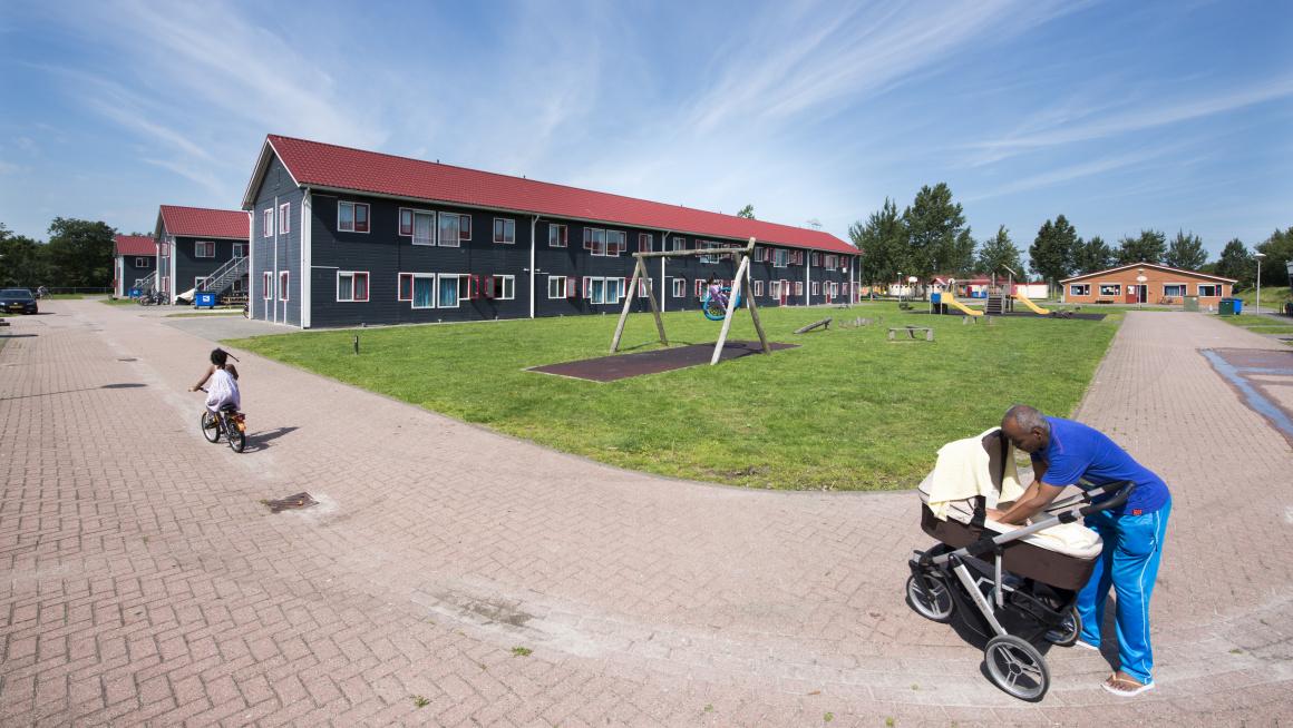Man met kinderwagen en fietsend meisje bij gezinslocatie Burgum