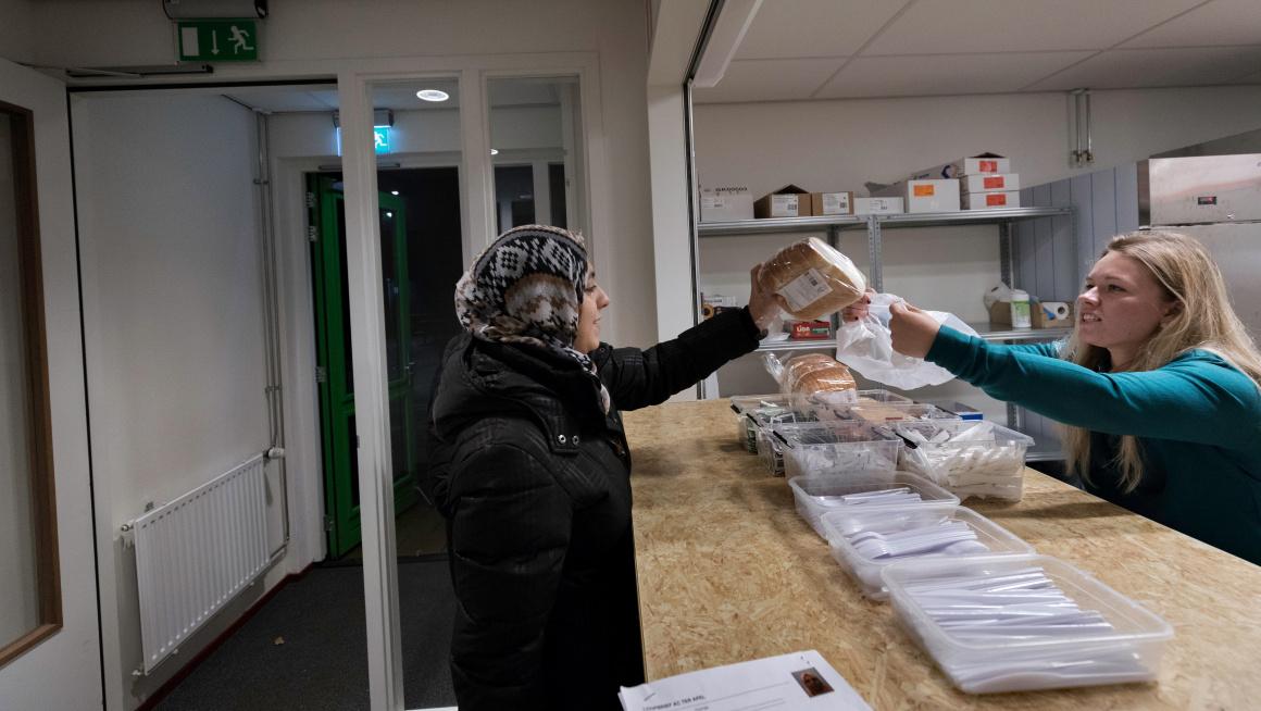 Vrouw ontvangt broodmaaltijd in de centrale ontvangstlocatie