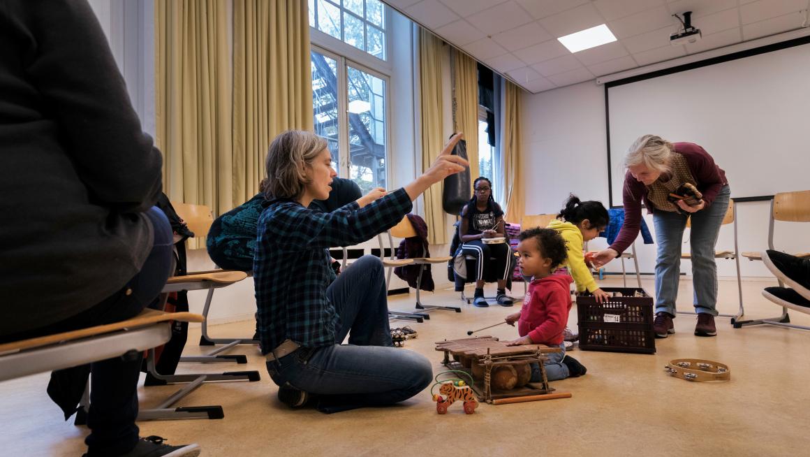 Kinderen doen mee aan een muziekactiviteit in het azc