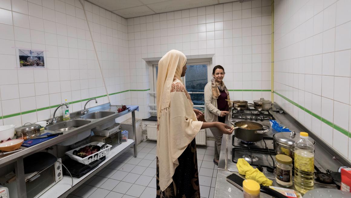 Twee vrouwen koken in de gemeenschappelijke keuken in het azc