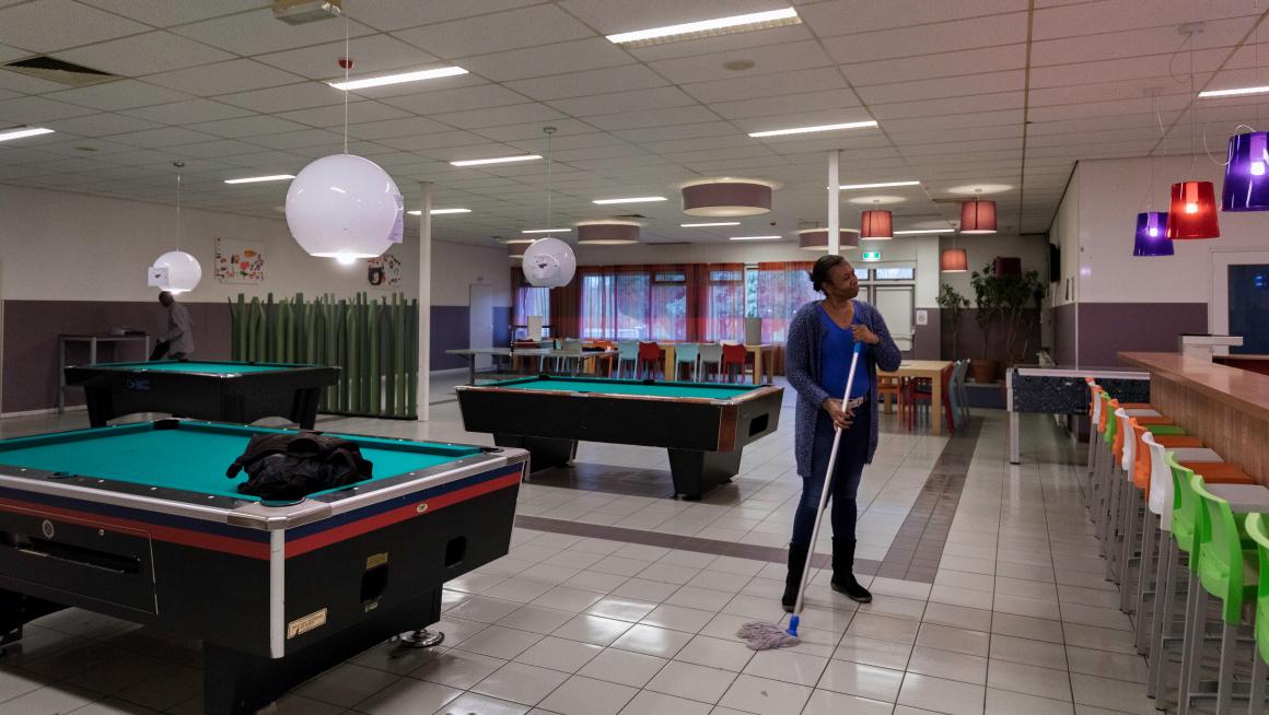 Een bewoner maakt de recreatieruimte van azc Dronten schoon