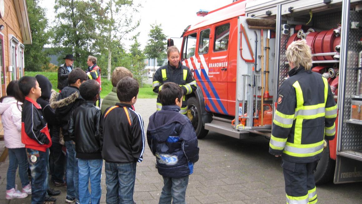Kinderen in het azc staan bij een brandweerauto en krijgen voorlichting