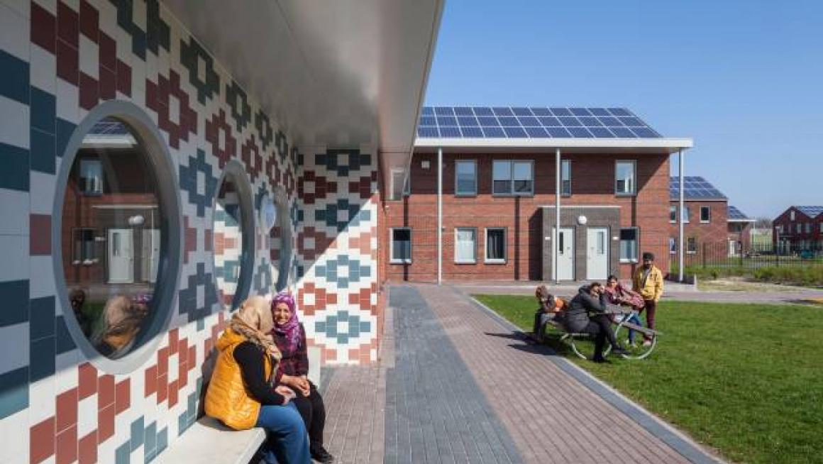 bewoners van azc voor het pand met zonnepanelen