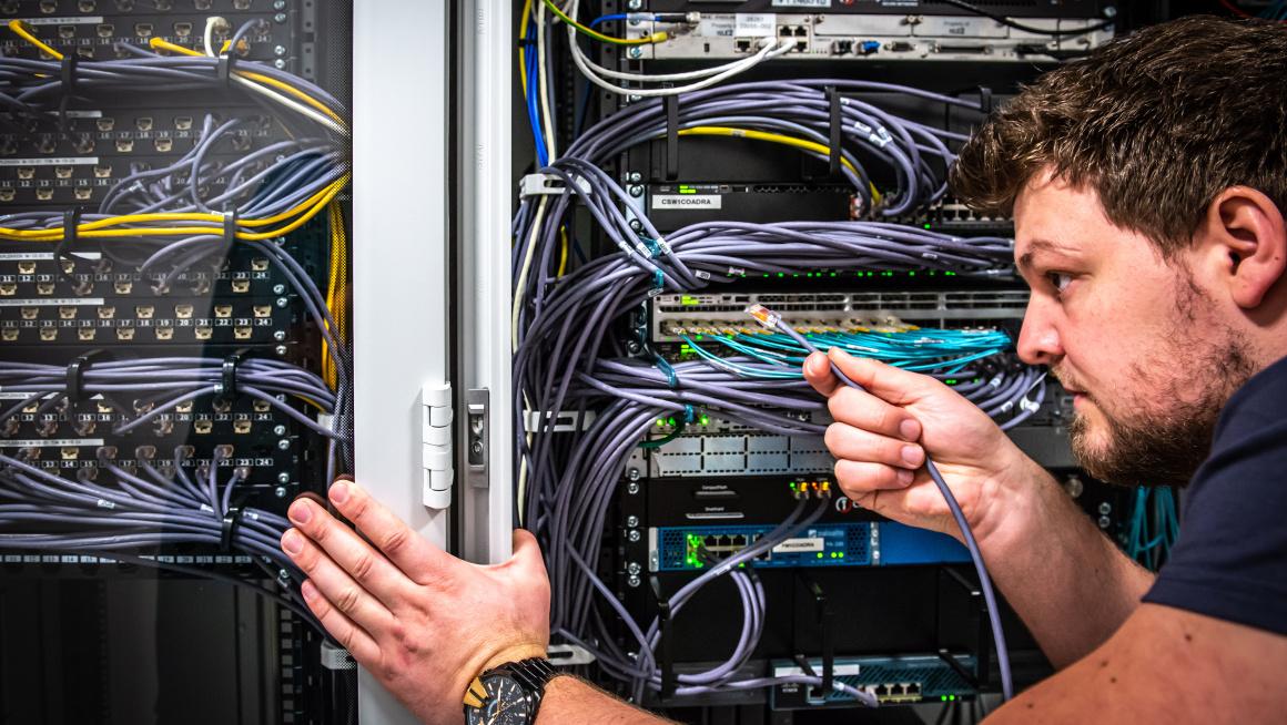 man aan het werk in netwerkkast