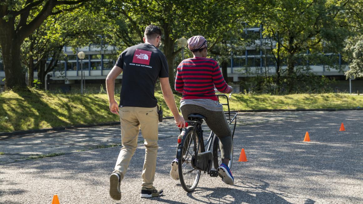 man helpt vrouw bij fietsen