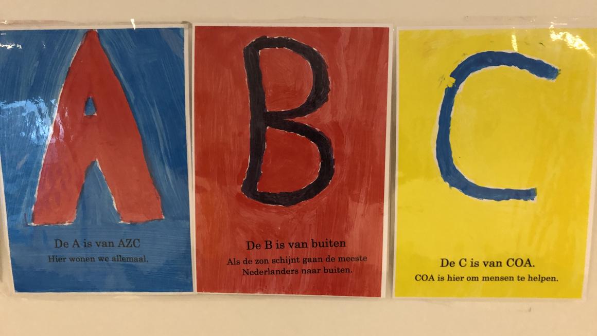 3 posters op de muur: een rode A op blauwe achtergrond, een zwarte B op een rode achtergrond en een blauwe C met gele achtergrond