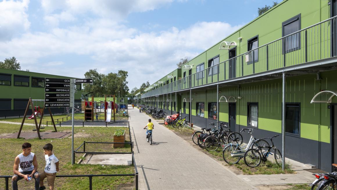 Groene gebouwen met twee verdiepingen, fietsen, gras en speeltuin met kinderen ervoor