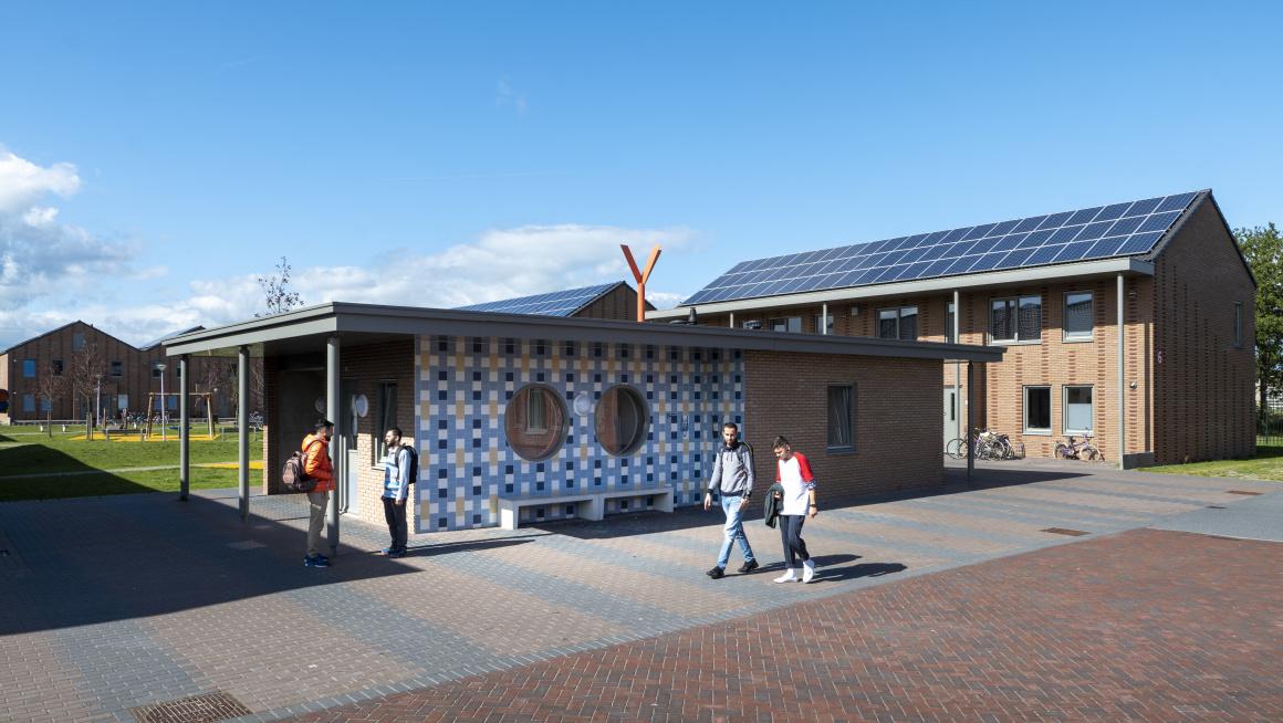 woongebouwen met twee verdiepingen met houten buitenkant en puntdaken met zonnepanelen, daarvoor een laag gebouw met plat dak en aan de buitenkant hout en wit met blauw en gele tegels, daarachter gras en rondom tegels waar vier bewoners lopen