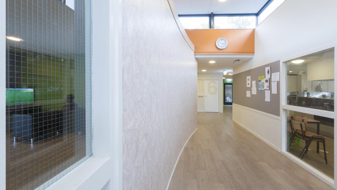 gang met witte muren en ramen met zicht op klaslokaal