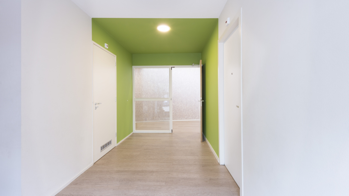 Gang met witte en groene muren en deuren