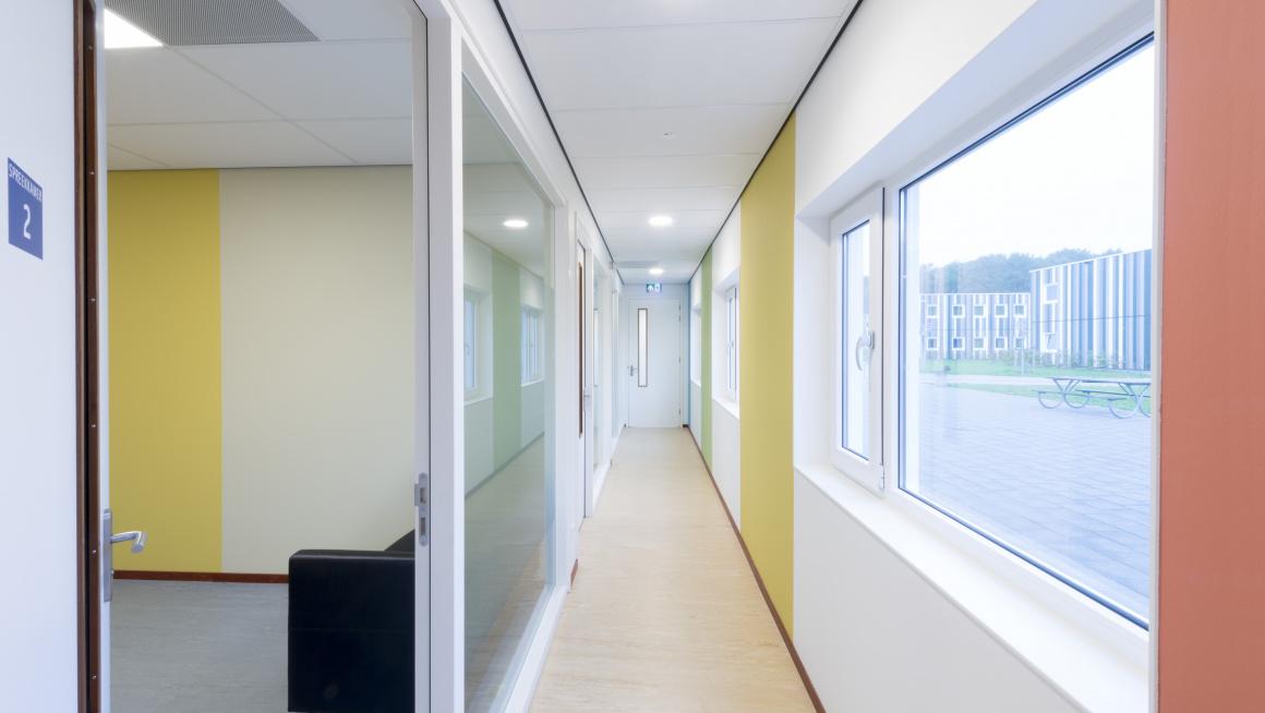 Gang met ramen en groene, gele en oranje verticale strepen op de muur
