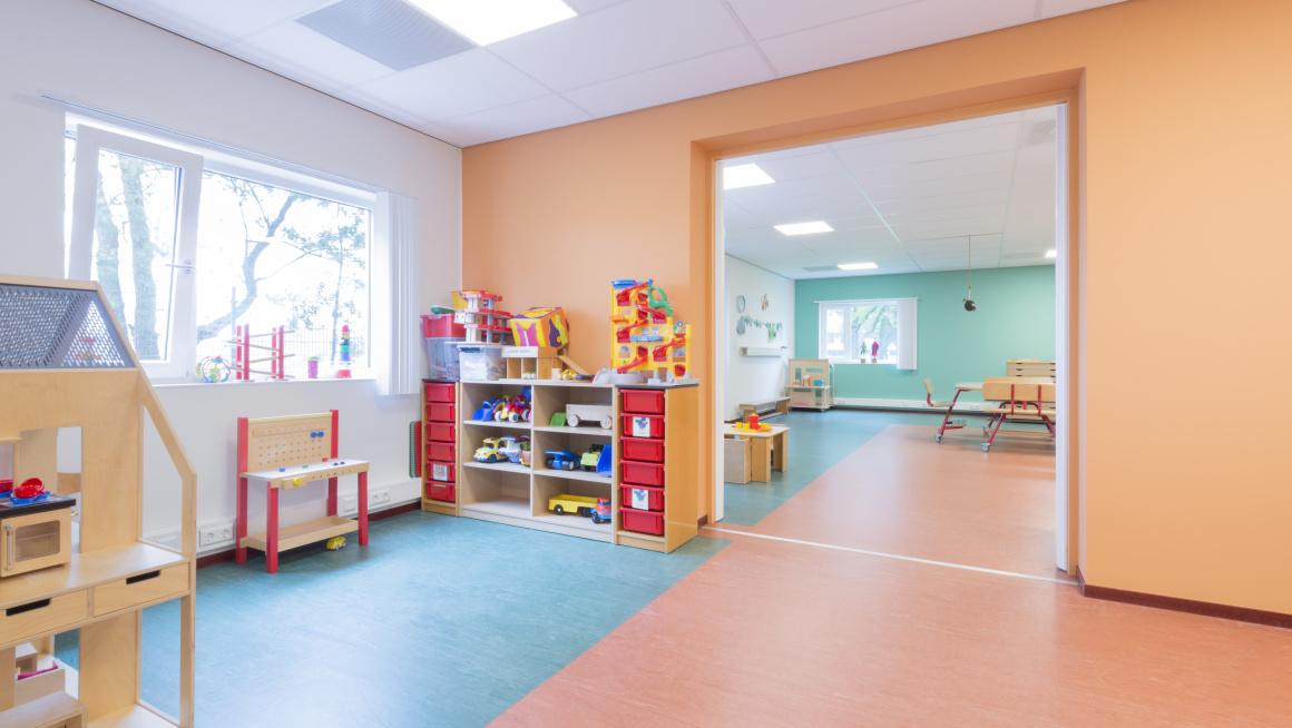 Peuterspeelzaal met vrolijke kleuren op de muren en vloer en divers speelgoed