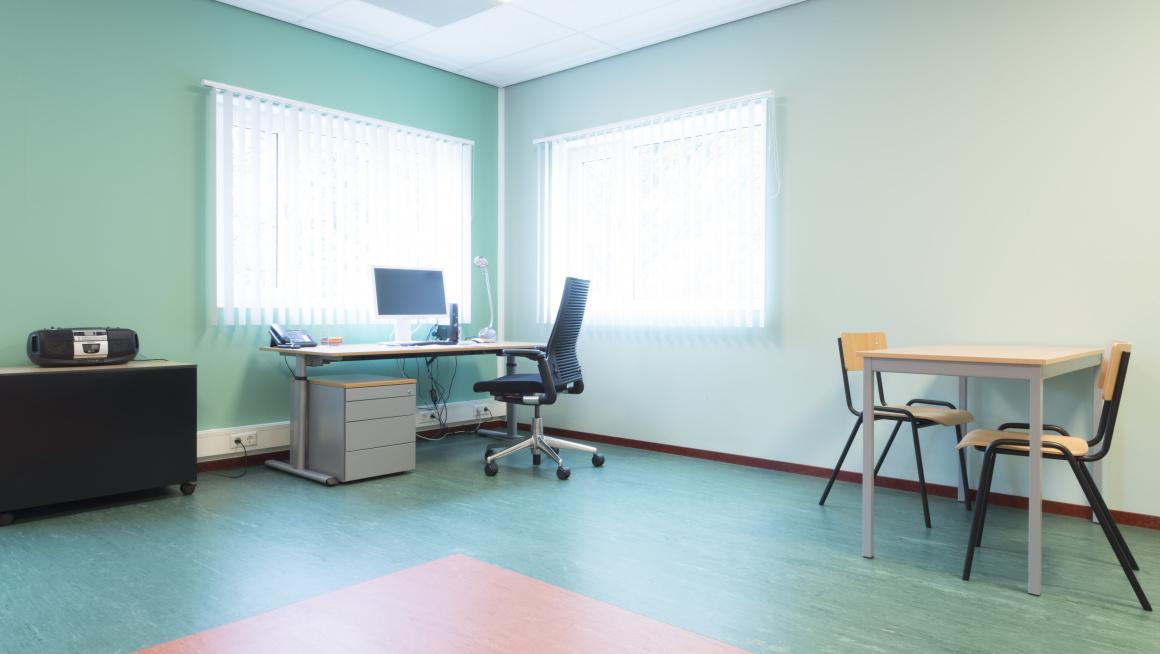 Kantoorruimte met bureau en bureaustoel, tafel en twee stoelen