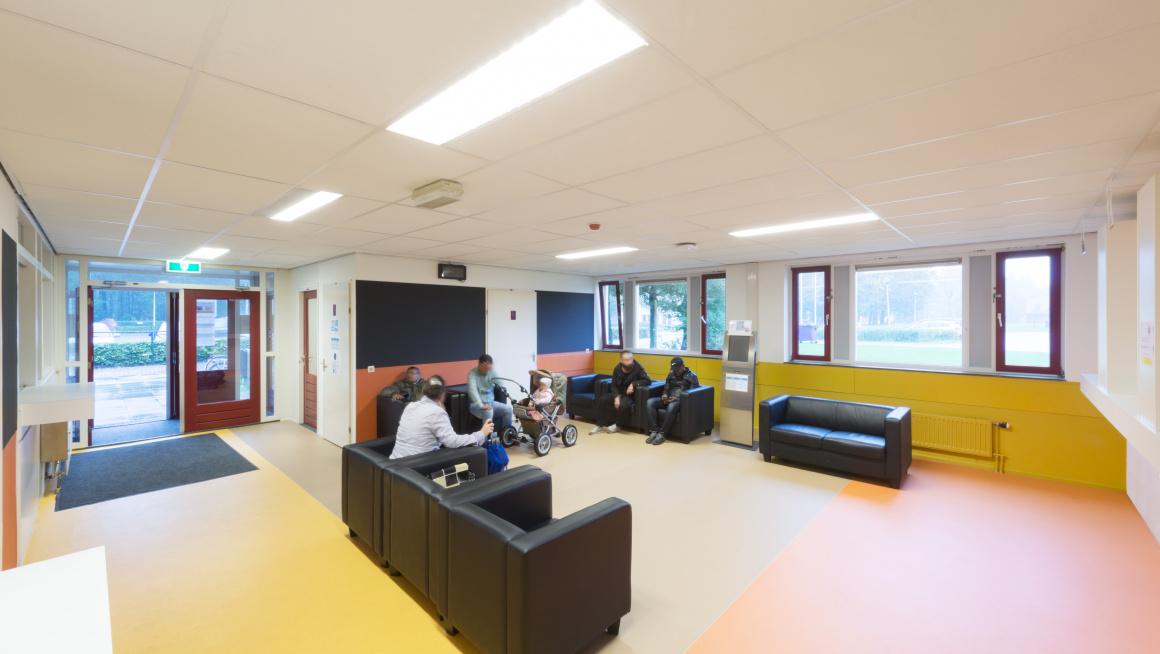 Ingang locatie, receptie, met geel en oranje op de muren en vloer en zwarte banken met bewoners die in gesprek zijn
