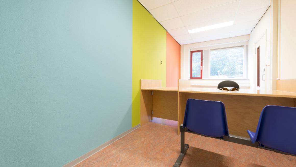 Spreekkamer met muur in blauw, geel en oranje, raam, bureau en blauwe stoelen