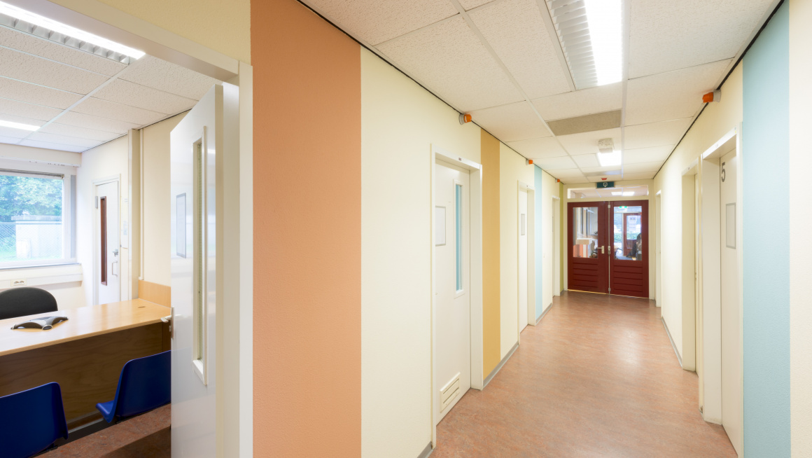 Gang met blauwe, gele en oranje verticale strepen op de muur en deuren aan weerszijden