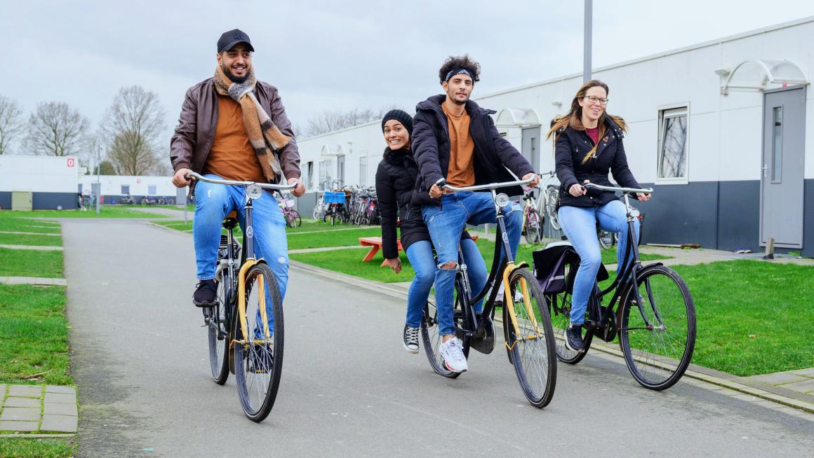 Drie asielzoekers en een COA-medewerker fietsen op het azc in Rotterdam