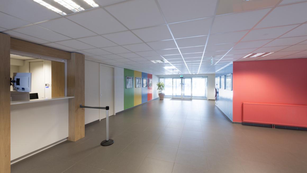 hal met recht een informatiebalie, de hal heeft bruine tegels op de vloer en de muren zijn wit met strepen in de kleuren rood, blauw, groen en geel
