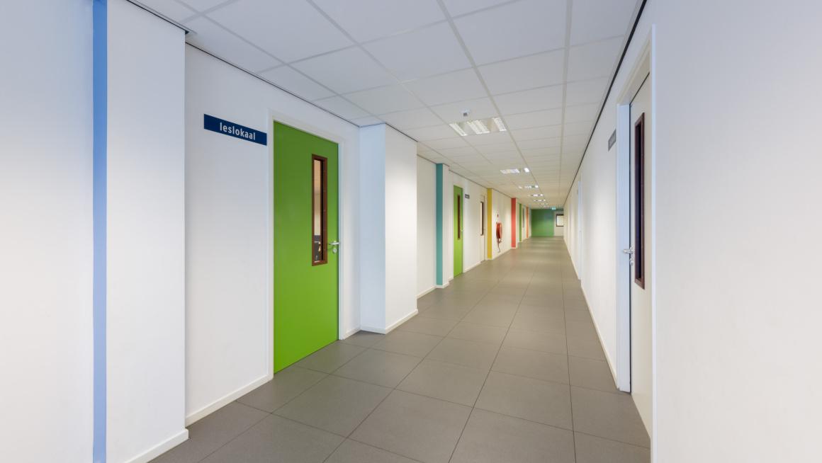 Gang met groene en witte deuren en op de witte muren gekleurde strepen