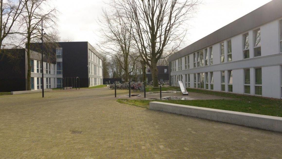rechts en links gebouwen, wit en grijs omrand, daarvoor bomen en wat gras en bestrating