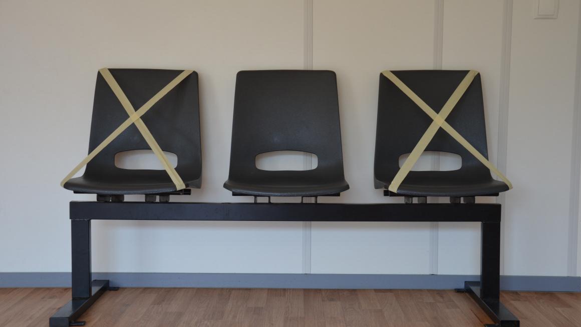 drie stoelen met op de twee buitenste een kruis zodat mensen daar niet gaan zitten