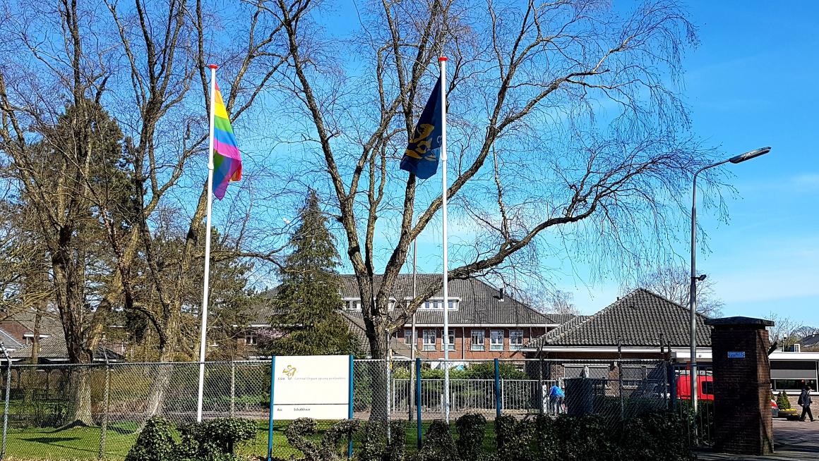 Ingang azc met op de achtergrond gebouwen, daarvoor bomen, daarvoor struiken met een bord met COA en azc Schalkhaar erop en daarchter twee vlaggenmasten met de COA-vlag en de lhbti-vlag