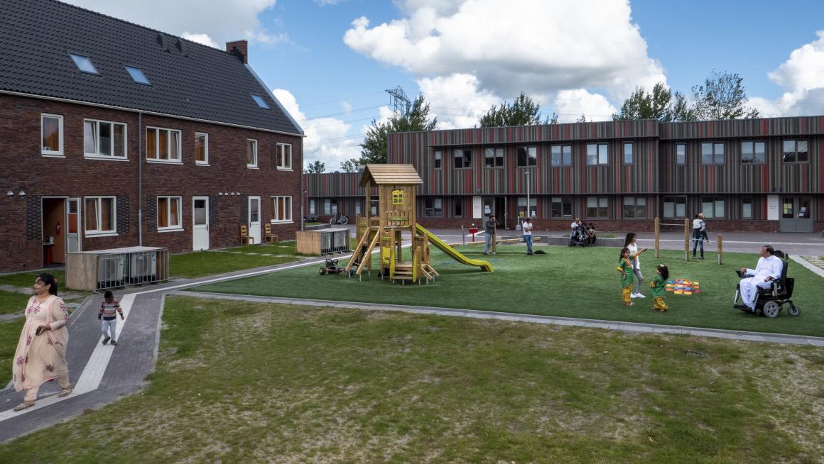 woongebouwen met daarvoor gras, speeltoestellen en paden met wandelende en spelende bewoners