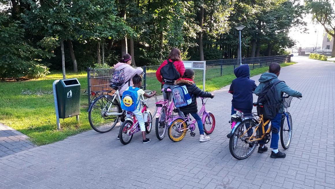 6 kinderen staan klaar op straat om met de fiets te vertrekken naar school