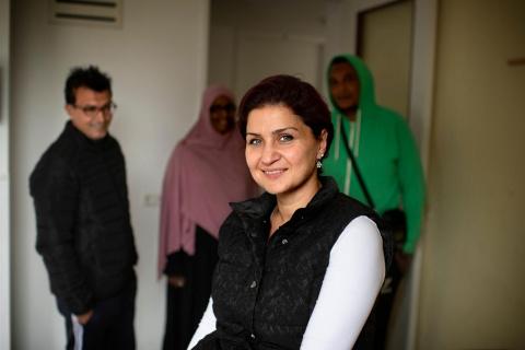 Woonbegeleider Kamar Kabakibi met nareizigers op achtergrond