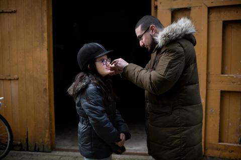 COA-medewerker helpt kind in azc met vastmaken paardrijcap