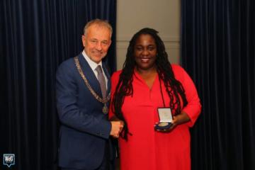 Burgemeester geeft gemeentepenning aan vrouw