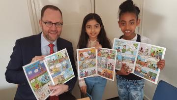 Milo en 2 meisjes houden stripboeken vast
