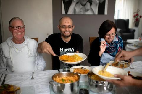 Asielzoeker eet een maaltijd met zijn buddy's