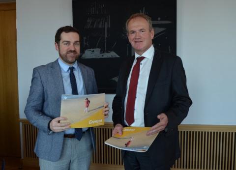 twee mannen presenteren het jaarverslag voor de foto