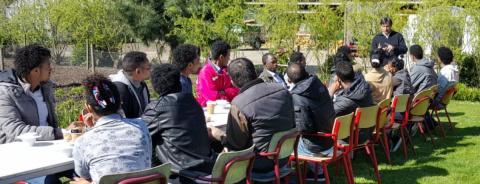 groep mensen zitten aan tafel en luisteren naar een man