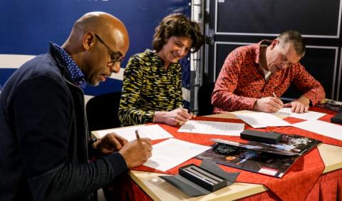 drie mensen ondertekenen de samenwerkingsovereenkomst