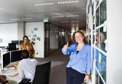 Vrouw geeft toelichting op foto's die aan de wand hangen