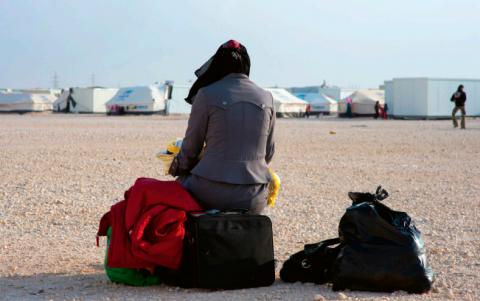 Vrouw met haar bagage in vluchtelingenkamp