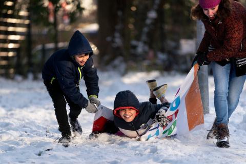 Asielzoekersinderen spelen buiten in de sneeuw