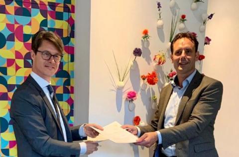 Joeri Kapteijns en burgemeester Harm Jan van Schaik van Harderwijk houden de net getekende bestuursovereenkomst vast.