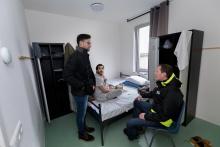 Woonbegeleider op kamerbezoek bij bewoner azc